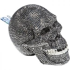 Geldkistje Skull Crystal Silver 32021 Een schedel met een levendige glitter - De Skull Crystal Silver spaarpot straalt een zeer glamoureus sprankelend leven uit, geen sombere dood. Myriaden steentjes vormen een schedel die schittert met ongekende helderheid. Het idee van deze schedel met zijn levendige schittering creëert een verrassend onconventioneel ontwerp dat barst van joie de vivre. Er is geen meer decoratieve manier om geld te besparen dan om het achterin dit ongewone object te plaatsen. Geleverd zonder bankbiljet. Kare Design